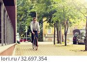 Купить «young man riding bicycle on city street», фото № 32697354, снято 21 августа 2016 г. (c) Syda Productions / Фотобанк Лори