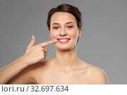 Купить «smiling young woman pointing to her mouth», фото № 32697634, снято 30 ноября 2019 г. (c) Syda Productions / Фотобанк Лори