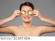 Купить «beautiful woman making eye mask of cucumbers», фото № 32697654, снято 30 ноября 2019 г. (c) Syda Productions / Фотобанк Лори