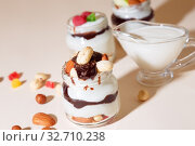 Купить «Sweet tasty milk curd creamy food in a glass jar of homemade breakfast. Cheesecake, English Trifle, Eton dessert, tiramisu, zuppa Inglese with nuts, almonds, cashews, hazelnuts, candied fruits and chocolate sauce», фото № 32710238, снято 14 декабря 2019 г. (c) Светлана Евграфова / Фотобанк Лори