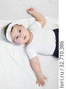 Calm baby boy lying on his back, dressed white t-shirt and bandage. Стоковое фото, фотограф Кекяляйнен Андрей / Фотобанк Лори