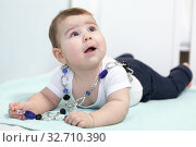 Купить «Six month old baby girl playing with beads, happy and smiling infant», фото № 32710390, снято 24 ноября 2019 г. (c) Кекяляйнен Андрей / Фотобанк Лори
