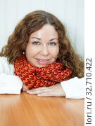 Smiling woman with red and orange neck scarf and white woolen sweater sitting at the table with clasped arms. Стоковое фото, фотограф Кекяляйнен Андрей / Фотобанк Лори