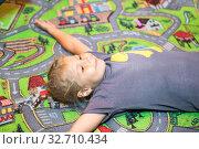 Happy playful girl 5-6 years old lying back on colorful carpet on floor. Стоковое фото, фотограф Кекяляйнен Андрей / Фотобанк Лори