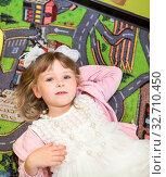 Happy cheerful girl 5-6 years old with white ribbon bow on head lying on her back on colorful carpet on floor. Стоковое фото, фотограф Кекяляйнен Андрей / Фотобанк Лори