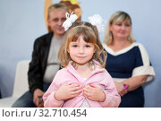 Young daughter standing in front of her parents sitting behind, little girl with father and mother. Стоковое фото, фотограф Кекяляйнен Андрей / Фотобанк Лори