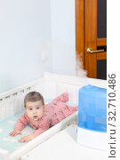 Air humidifying in children room, baby girl lying in white crib with humidifier in use next to bed. Стоковое фото, фотограф Кекяляйнен Андрей / Фотобанк Лори