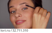 face of beautiful young woman applying mascara. Стоковое видео, видеограф Syda Productions / Фотобанк Лори