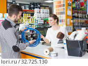 Купить «Girl seller helping man customer at the counter», фото № 32725130, снято 17 мая 2018 г. (c) Яков Филимонов / Фотобанк Лори