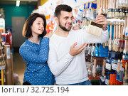 Купить «Loving couple deciding on brush for decorating house», фото № 32725194, снято 9 марта 2017 г. (c) Яков Филимонов / Фотобанк Лори
