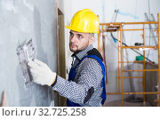 Купить «Workman in the helmet is plastering the wall», фото № 32725258, снято 3 июня 2017 г. (c) Яков Филимонов / Фотобанк Лори