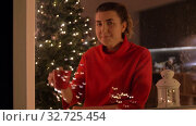 Купить «happy woman drinking coffee on christmas at home», видеоролик № 32725454, снято 16 декабря 2019 г. (c) Syda Productions / Фотобанк Лори