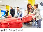 Familie und andere Passagiere holen ihre Koffer vom Gepäckband nach der Reise Ankunft. Стоковое фото, фотограф Zoonar.com/Robert Kneschke / age Fotostock / Фотобанк Лори