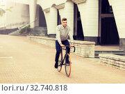 Купить «young man riding bicycle on city street», фото № 32740818, снято 21 августа 2016 г. (c) Syda Productions / Фотобанк Лори