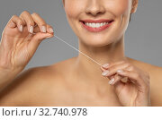 smiling woman with dental floss cleaning teeth. Стоковое фото, фотограф Syda Productions / Фотобанк Лори