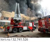 Купить «Пожарная команда тушит пожар пожарная лестница», фото № 32741526, снято 13 декабря 2019 г. (c) Кузнецов Максим / Фотобанк Лори