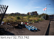 Great Britain, Northern Ireland, Belfast - Protestant part of West Belfast - neglected, burnt square after the bonfire of Orangemens Day, in the back Peace Wall (2019 год). Редакционное фото, агентство Caro Photoagency / Фотобанк Лори