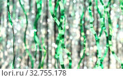 Green tinsel on silver bokeh background. Beautiful dynamic background in shining lights and sparkling particles. Festive mood. Christmas or holiday theme. Стоковое видео, видеограф Dmitry Domashenko / Фотобанк Лори