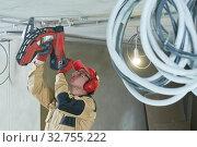 Купить «electrician service. Installer nailing tube holder for cable conduit», фото № 32755222, снято 11 декабря 2019 г. (c) Дмитрий Калиновский / Фотобанк Лори