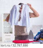 Купить «The inattentive husband burning clothing while ironing», фото № 32787886, снято 19 декабря 2017 г. (c) Elnur / Фотобанк Лори