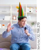 Купить «Funny man singing songs in karaoke at home», фото № 32788270, снято 29 марта 2017 г. (c) Elnur / Фотобанк Лори
