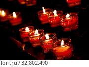 Купить «Red translucent glass candles burning in dark church, close up, high angle view», фото № 32802490, снято 31 марта 2020 г. (c) easy Fotostock / Фотобанк Лори