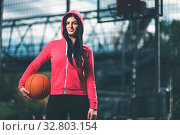 Young female basketball player training outdoors on a local court. Стоковое фото, фотограф Zoonar.com/Tomas Anderson / easy Fotostock / Фотобанк Лори