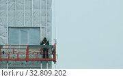 A man worker lifting up on the building for continue constructing. Стоковое видео, видеограф Константин Шишкин / Фотобанк Лори