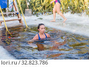 Russia Samara December 2019: young beautiful woman dives into an ice hole on a winter day. Редакционное фото, фотограф Акиньшин Владимир / Фотобанк Лори