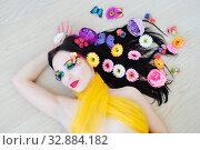 Купить «Girl with bright makeup lies in the flowers», фото № 32884182, снято 24 февраля 2019 г. (c) Арестов Андрей Павлович / Фотобанк Лори