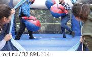 Купить «Two men in big boxing gloves boxing on inflatable ring in outdoor amusement park», видеоролик № 32891114, снято 12 ноября 2019 г. (c) Яков Филимонов / Фотобанк Лори