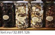 Купить «Various dried mushrooms in closed glass jars for sale on counter in store», видеоролик № 32891126, снято 31 марта 2020 г. (c) Яков Филимонов / Фотобанк Лори