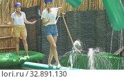 Купить «Young people try to walk the wet log in the theme park», видеоролик № 32891130, снято 1 июля 2020 г. (c) Яков Филимонов / Фотобанк Лори