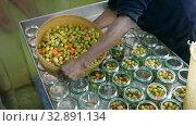 Afro-american man fills ripe olives in glass jars for canning. Стоковое видео, видеограф Яков Филимонов / Фотобанк Лори