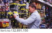 Купить «Male customer choose locksmith tools at hardware store», видеоролик № 32891150, снято 8 апреля 2020 г. (c) Яков Филимонов / Фотобанк Лори