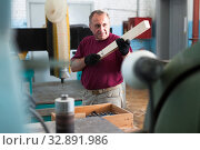 Купить «Positive craftsman working on a thicknessing machine», фото № 32891986, снято 22 февраля 2020 г. (c) Яков Филимонов / Фотобанк Лори