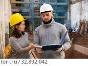 Engineers discussing blueprint at construction site. Стоковое фото, фотограф Яков Филимонов / Фотобанк Лори