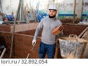 Купить «Man installing brick wall», фото № 32892054, снято 25 февраля 2020 г. (c) Яков Филимонов / Фотобанк Лори