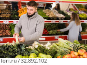 Купить «Adult man is choosing leek and celery in the grocery store», фото № 32892102, снято 20 ноября 2019 г. (c) Яков Филимонов / Фотобанк Лори