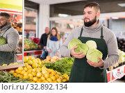 Купить «Male shop assistant in an apron carries fresh cabbage», фото № 32892134, снято 20 ноября 2019 г. (c) Яков Филимонов / Фотобанк Лори