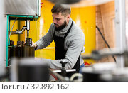 Young man working on olive oil bottling line. Стоковое фото, фотограф Яков Филимонов / Фотобанк Лори