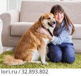 Купить «Happy woman dog owner at home with golden retriever», фото № 32893802, снято 5 марта 2018 г. (c) Elnur / Фотобанк Лори
