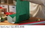 Купить «hands wrapping christmas gift into paper at home», видеоролик № 32893898, снято 18 декабря 2019 г. (c) Syda Productions / Фотобанк Лори