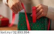 Купить «hands packing christmas gift and tying bow», видеоролик № 32893994, снято 18 декабря 2019 г. (c) Syda Productions / Фотобанк Лори