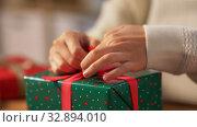 Купить «hands packing christmas gift and tying bow», видеоролик № 32894010, снято 18 декабря 2019 г. (c) Syda Productions / Фотобанк Лори