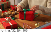 hands packing christmas gift and tying green bow. Стоковое видео, видеограф Syda Productions / Фотобанк Лори