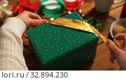 Купить «hands packing christmas gift and choosing bow», видеоролик № 32894230, снято 18 декабря 2019 г. (c) Syda Productions / Фотобанк Лори