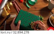 Купить «hands packing christmas gift and choosing bow», видеоролик № 32894278, снято 18 декабря 2019 г. (c) Syda Productions / Фотобанк Лори