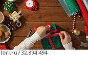 Купить «hands packing christmas gift and tying bow», видеоролик № 32894494, снято 18 декабря 2019 г. (c) Syda Productions / Фотобанк Лори