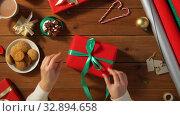 Купить «hands packing christmas gift and tying green bow», видеоролик № 32894658, снято 18 декабря 2019 г. (c) Syda Productions / Фотобанк Лори